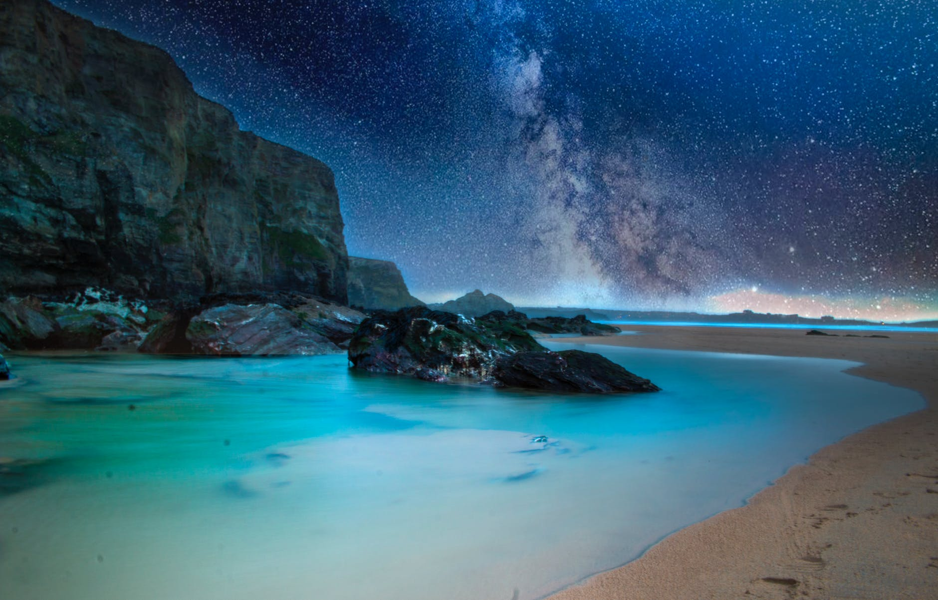 ocean with rock formation under starry night